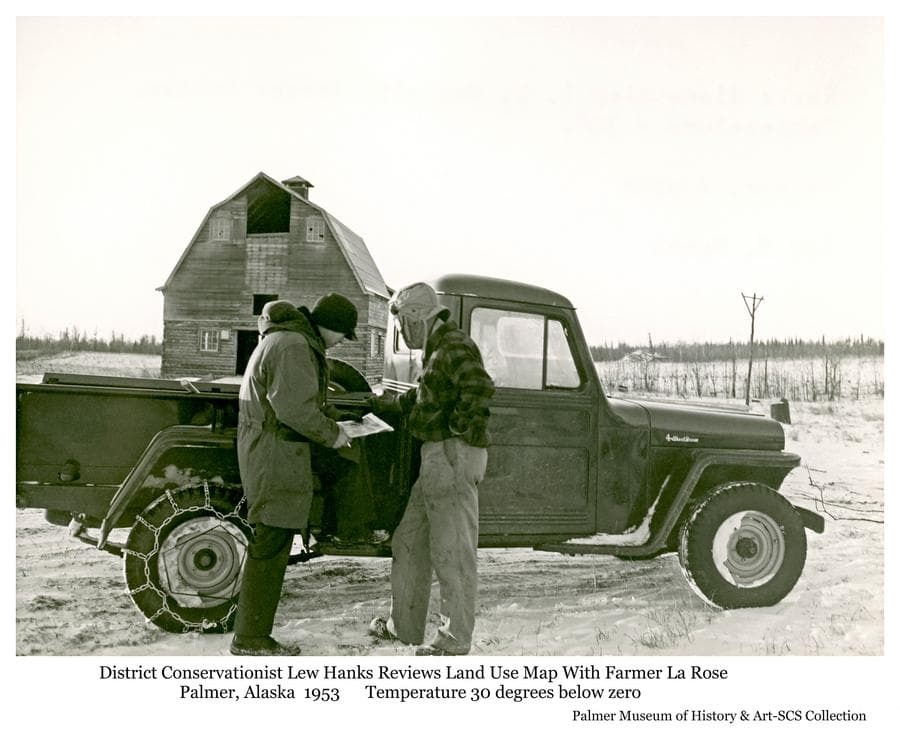District Conservationist Lew Hanks reviews a land use map with Matanuska Valley farmer and Colonist Henry LaRose during the winter of 1953.  Temperature was noted to be minus 30 degrees.
