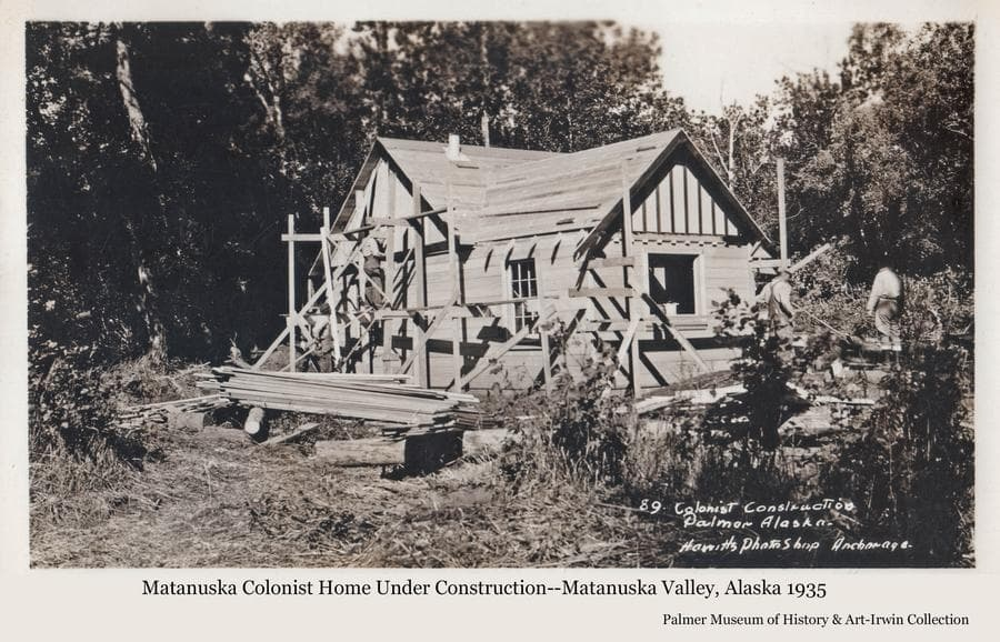 """Image shows a Colony home under construction.  Homes not built of logs were referred to by the government as """"cottages"""".  Three men are visible with scaffolding on the outside of the house.  Lumber and considerable debris are apparent in the yard.  Heavy forest is the backdrop."""