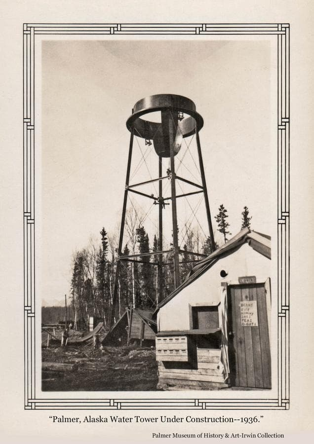 """Image prominently shows the water tower under construction in middle ground.  At least two people are visible on the tower and additional tower parts are visible on the ground.  A tent is in foreground who's function is undetermined.  The wood door holds a sign proclaiming """"Beans, Rice, Hominy, Salt, Peas, and R-Oats"""".  Above the door is an """"OFFICE"""" sign.  A window space next to the door, and an outside shelf suggest items may have been dispensed here.  A slotted box below the shelf had an unknown function."""