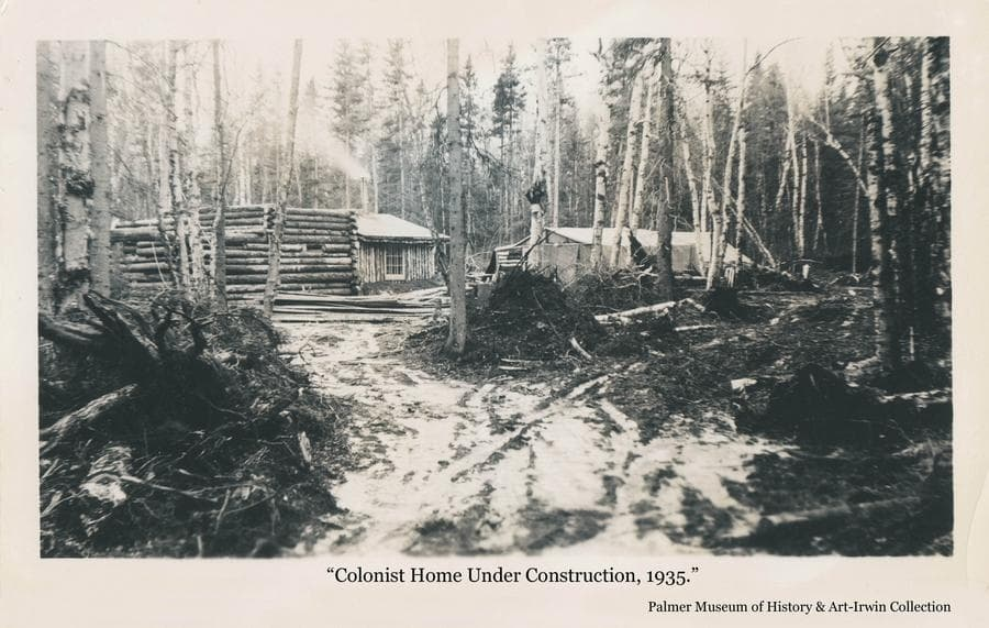 Image is a heavily wooded setting with a rough access roadway through stump piles leading to a partially visible vertical-log house with smoke coming from the chimney.  In front of the house is a partially constructed log structure and to the right is a tent.  Scattered snow on the ground may indicate the image was made in early winter.