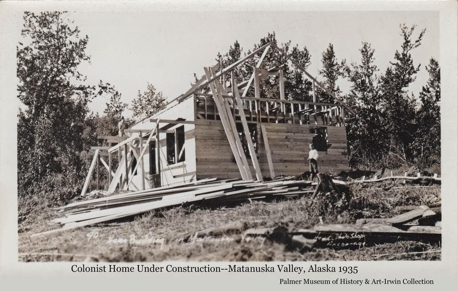 Image is of a frame house under construction.  A man is visible up on scaffolding and a boy is on the ground.  Lumber is stacked on the ground and leaning against the building.  Cottonwood trees form the backdrop.