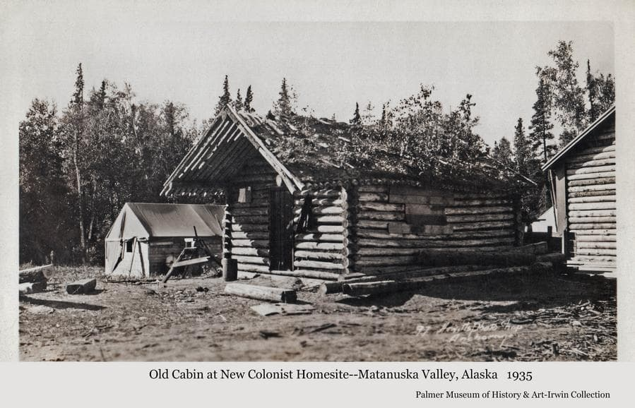 Image shows an old log cabin in foreground with a tent behind and a portion of a new colony house at right.  A grindstone is visible near the tent.  Heavy forest is the backdrop.