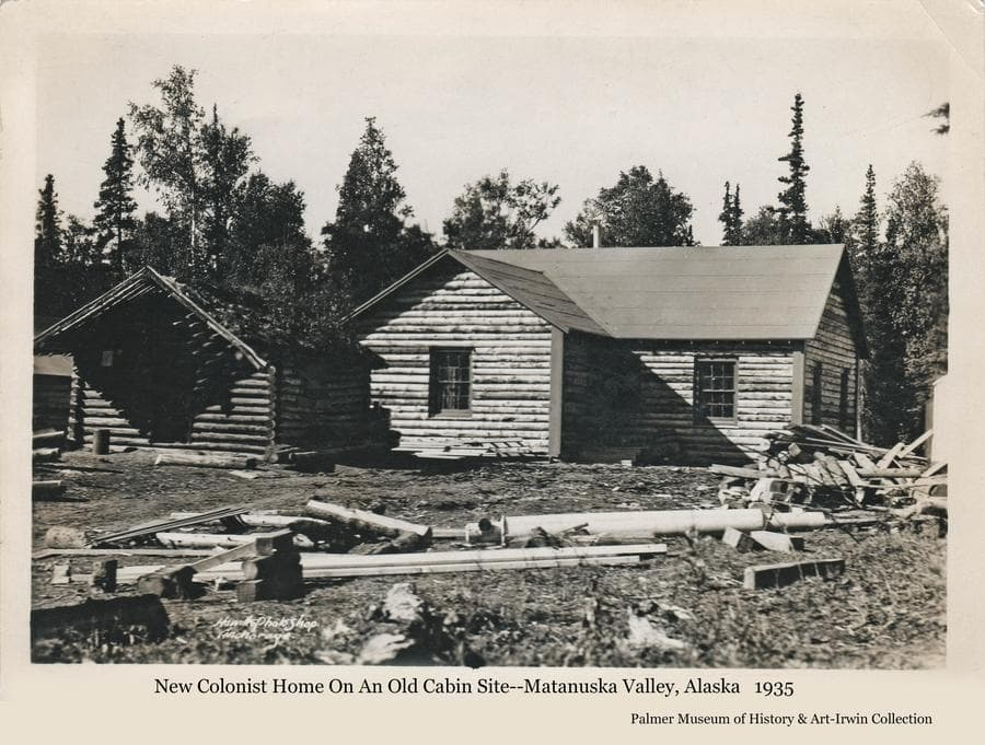 Image shows an old log cabin in middle ground with a new colony house just behind and at right.  Lumber and other wood is in foreground.  Heavy forest is the backdrop.