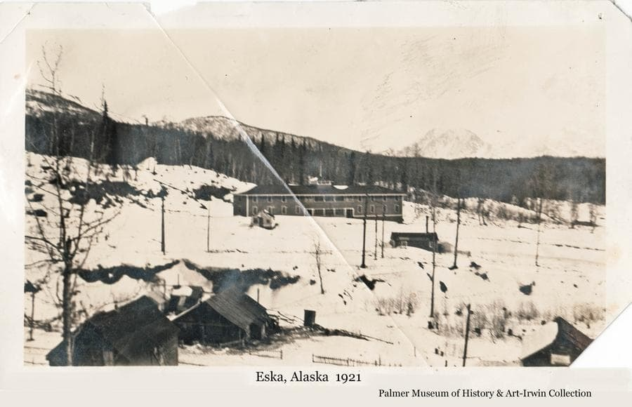 Image is a winter view of the coal-mining community of Eska located in the Matanuska River Valley north of Palmer, Alaska.  A large residential or office building and several houses are visible.  Power poles are evident.  The land is cleared around the buildings with heavy forest beyond.  Mountains are faintly visible in background.