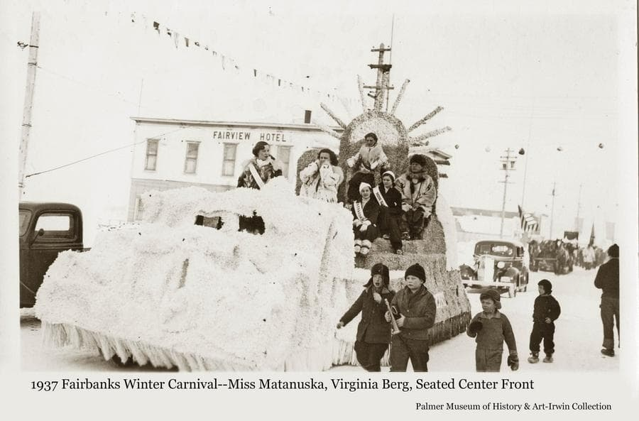 """Image is of a parade float at the 1937 Fairbanks Winter Carnival.  Children are walking in the foreground, several women are riding on the float, several automobiles are evident, flags are flying and the Fairview Hotel is identified.  Miss Virginia Berg of Palmer is riding on the float as the """"Miss Matanuska"""" entry in the festival Queen contest, seated in the center front."""