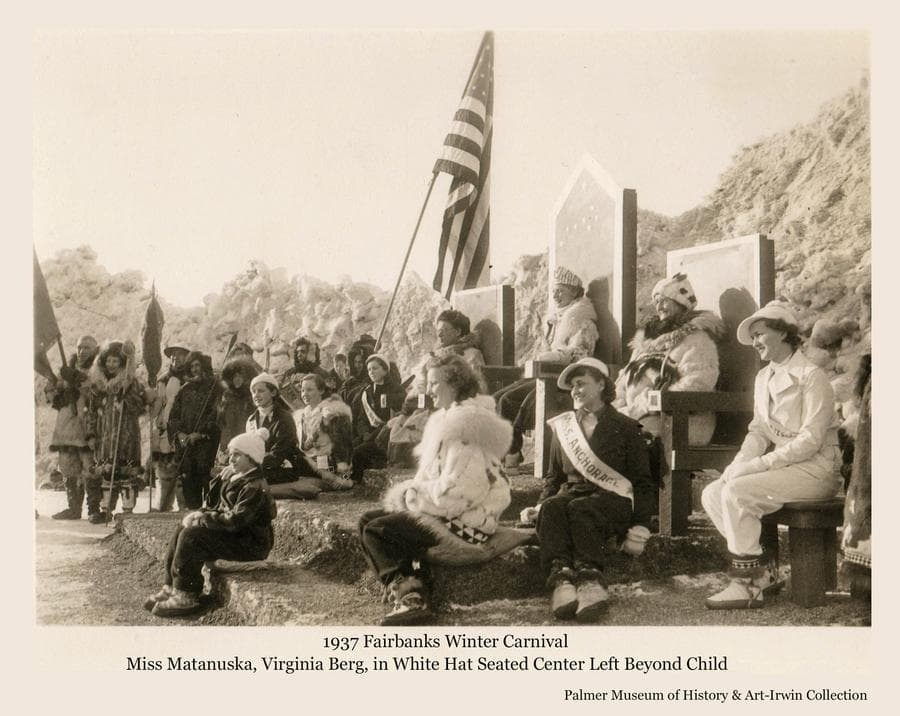 """Image is of the royal court at the 1937 Fairbanks Winter Carnival.  Several women and men are gathered.  Miss Virginia Berg of Palmer is the """"Miss Matanuska"""" entry in the festival Queen contest and is seen seated in the center left of the image behind the child.  The American flag is prominent."""
