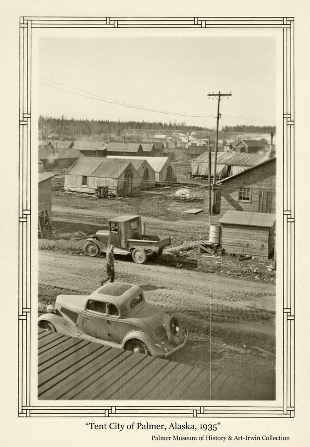 """Image is of automobiles, tents and other buildings of """"Tent City"""" in the earliest days of the Colony establishment at Palmer.  A man is seen walking on the street.  Power poles are evident."""