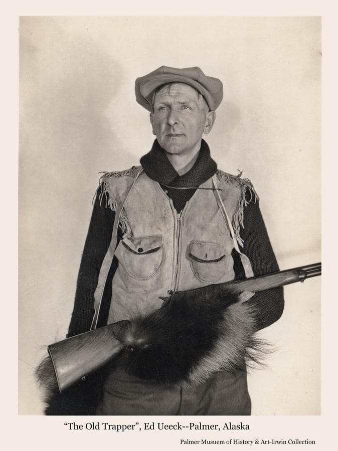 """Image is of a man, identified as trapper Ed Ueeck, wearing wolverine mittens and holding a rifle.  Mr. Ueeck was a resident of Palmer for many years and trapped around the Sheep Mountain area at the head of Matanuska River.  He is the subject of a book, """"The Man From Sheep Mountain"""", by his nephew Kim A. Ueeck."""