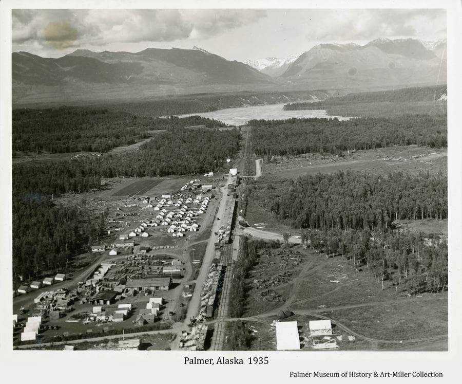 """Image is a northerly oblique view over the """"Tent City"""" buildings, railroad and roads of the Matanuska Colony center of operation at Palmer.  Heavy forest is prominent around homestead clearings in middle ground, the Matanuska River is evident in far middle ground and the Talkeetna Mountains are in background."""