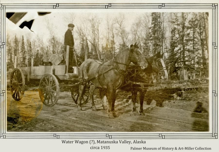 Image is a winter view of a two-horse team hitched to a four-wheel wagon on a graded dirt road.  In the wagon stands an unidentified man with wooden barrels or boxes covered by a tarp.  A small white crock is also visible at the man's feet.  Scattered forest forms the backdrop in middle ground.
