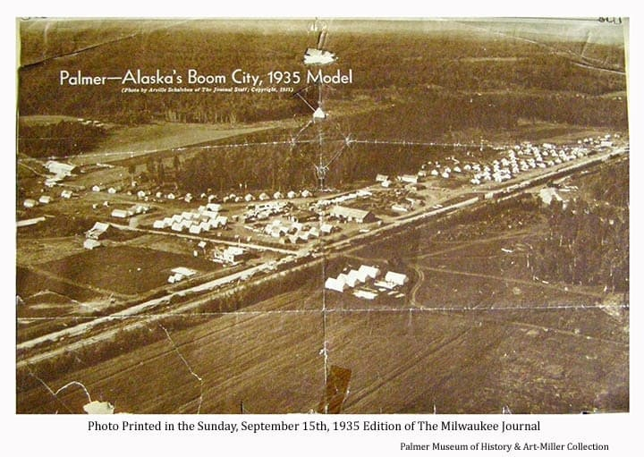 """Image is of a photo printed in the September 15th, 1935 issue of the Milwaukee Journal showing a northwesterly oblique view over the """"Tent City"""" buildings, railroad and roads of the Matanuska Colony center of operation at Palmer.  Heavy forest is prominent around homestead clearings in middle ground and cultivated land in foreground."""