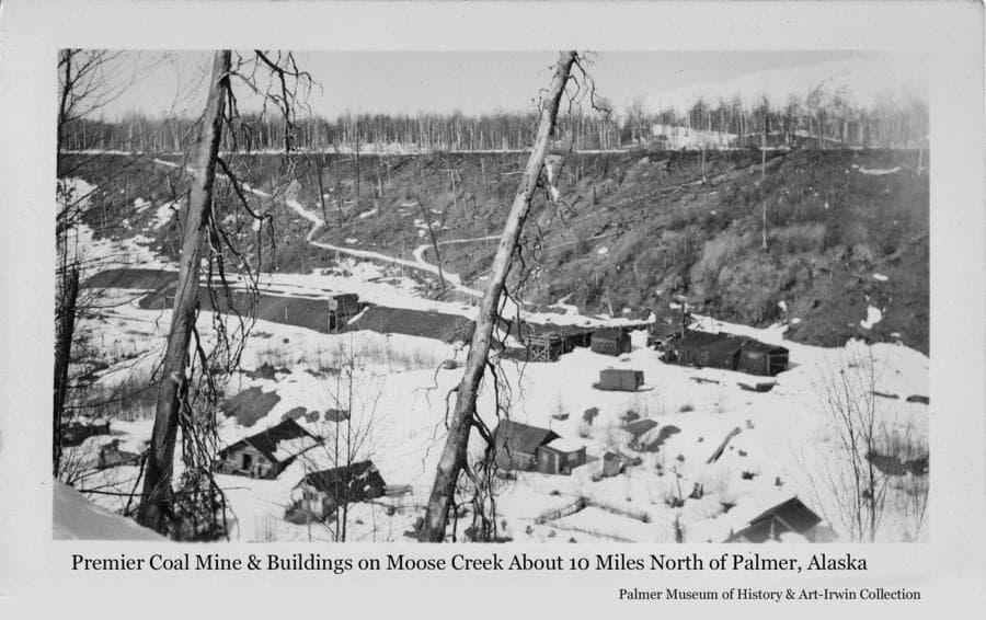 Image is a winter view down into the creek bottom showing cabins and other buildings associated with the Premier coal mine on Moose Creek about ten miles north of Palmer.  Foot trails are visible descending the far stream bank from flat land above.