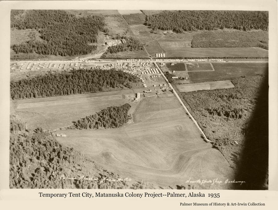 """Image is a high oblique view over the """"Tent City"""" buildings, tents, railroad and roads of the Matanuska Colony center of operation at Palmer.  Heavy forest is prominent around homestead clearings.  John Bugge's homestead buildings are evident and his fields are prominent."""