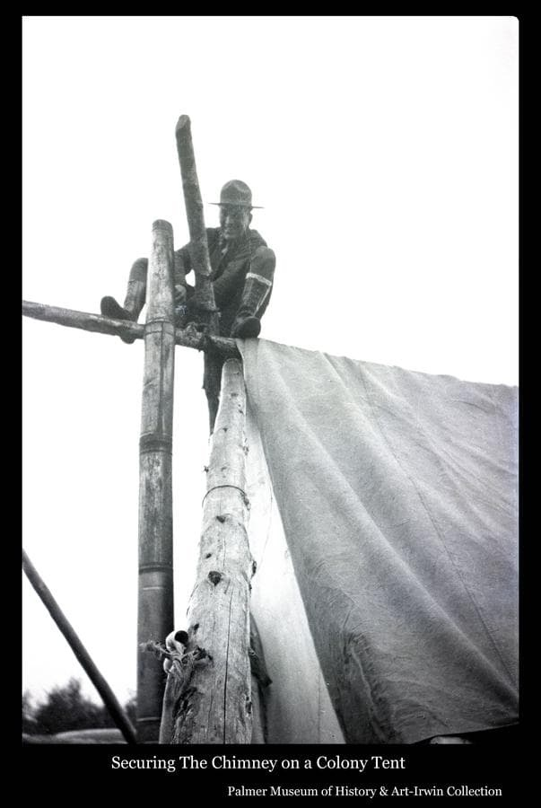 Image is of a man perched atop tent poles at the ridge pole while he wires the chimney pipe to the ridge pole to secure it.