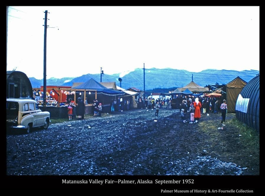 Photo is a color image of the 1952 Matanuska Valley Fair midway showing people, gaming tents, parts of Quonset Huts and a car.  Mountains are in background.