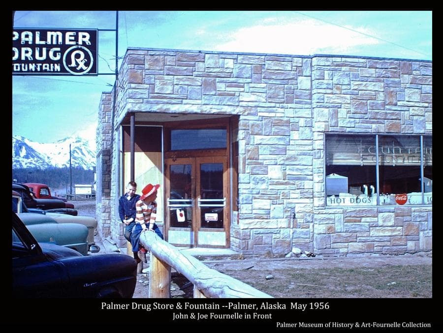 This color image shows the south side of Palmer Drug Store with two young boys, identified as John and Joe Fournelle, sitting on a log rail in front.  Several parked cars are partially visible at left.  Signs are evident.  Snow-clad mountains are visible in background.