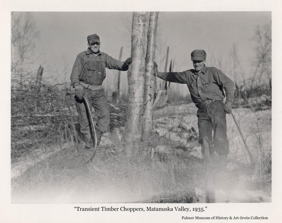 """Two men, identified as transient laborers associated with the Matanuska Colony project, pause in their job of clearing land of trees to make way for construction of Colony development.  One man holds a bow saw, also called as """"Swede Saw"""", the other holds an ax."""