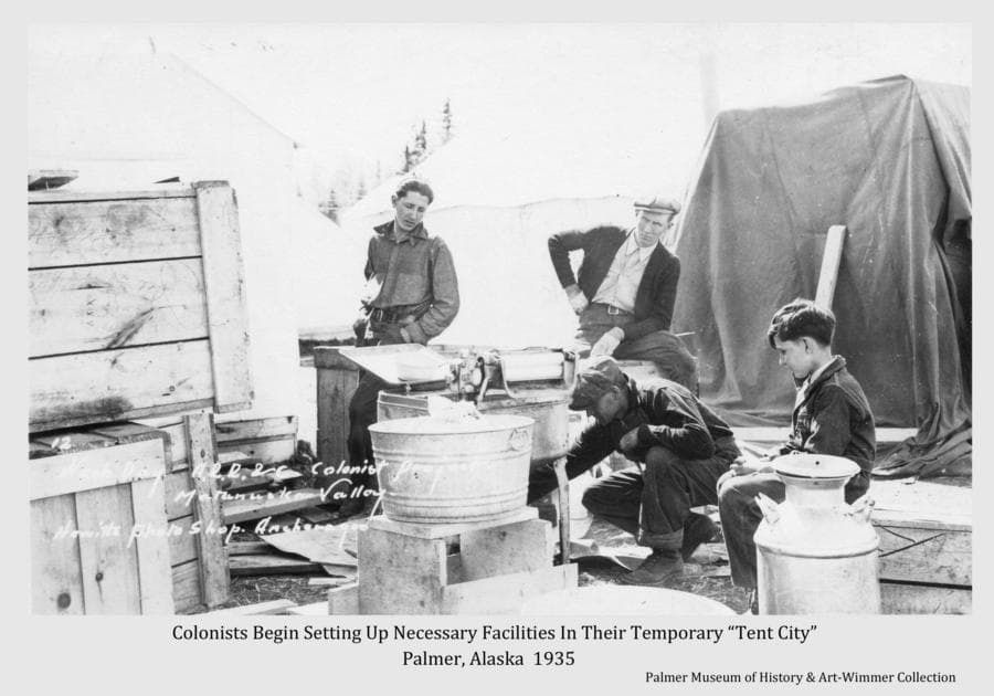 "Image shows a man adjusting the motor of a gas powered washing machine while two other men and a boy look on.  The setting is amongst tents, wooden crates and other material of the early stages of life in the Colony temporary ""Tent City""."