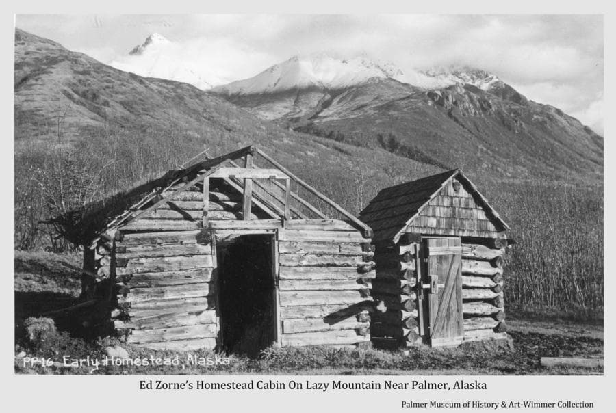 Image is of a log cabin and outhouse, identified as originally belonging to homesteader Ed Zorn.  Location is on the lower slopes of Lazy Mountain east of Palmer, land later owned by Frank Clark.