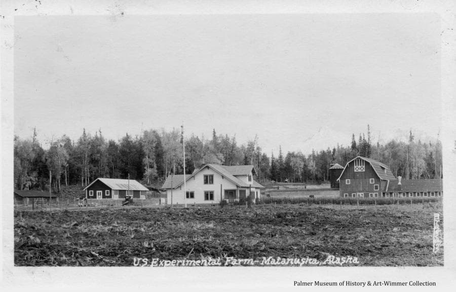 Image is of a tilled field in foreground before several of the buildings of the Matanuska Experiment Farm with heavy forest beyond.  Date of the photo is uncertain, but based partly on the automobile visible at left of the house, it's estimated to be in the early 1930's.