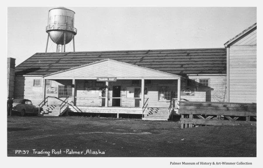 Image is a summer view of the Matanuska Colony (Co-op) Trading Post.  The building was constructed initially as a warehouse and vacated when another warehouse was built behind it in about 1940.  The store then moved into the larger space from the smaller building across the street.  The store served the Colonists and other residents of the surrounding area.