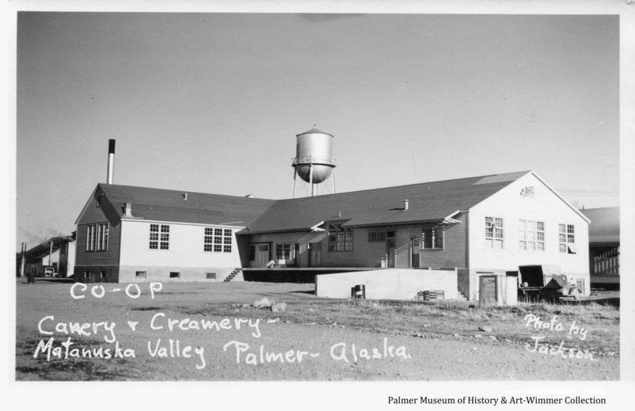 Image is a summer view of the Matanuska Colony (Co-op) creamery and cannery building.  The water tower and powerhouse smoke stack are visible behind.