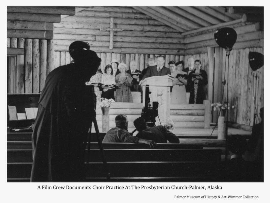 Image is of a Warner Brothers film crew documenting choir practice in the log Presbyterian Church in Palmer.  Identified members of the choir are Rev. Bert Bingle at the pulpit, Harry Wimmer, Howard Estelle and Ruth DeArmond Estelle at right.
