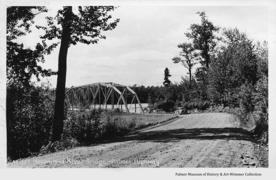 Image shows the highway leading from Anchorage and the Butte approaching the Matanuska River steel bridge sometime after it was constructed in 1934.  A car is visible approaching the bridge on the gravel road.  Trees and brush are prominent on both sides of the road.  The river is partially visible through the latticework of the bridge.