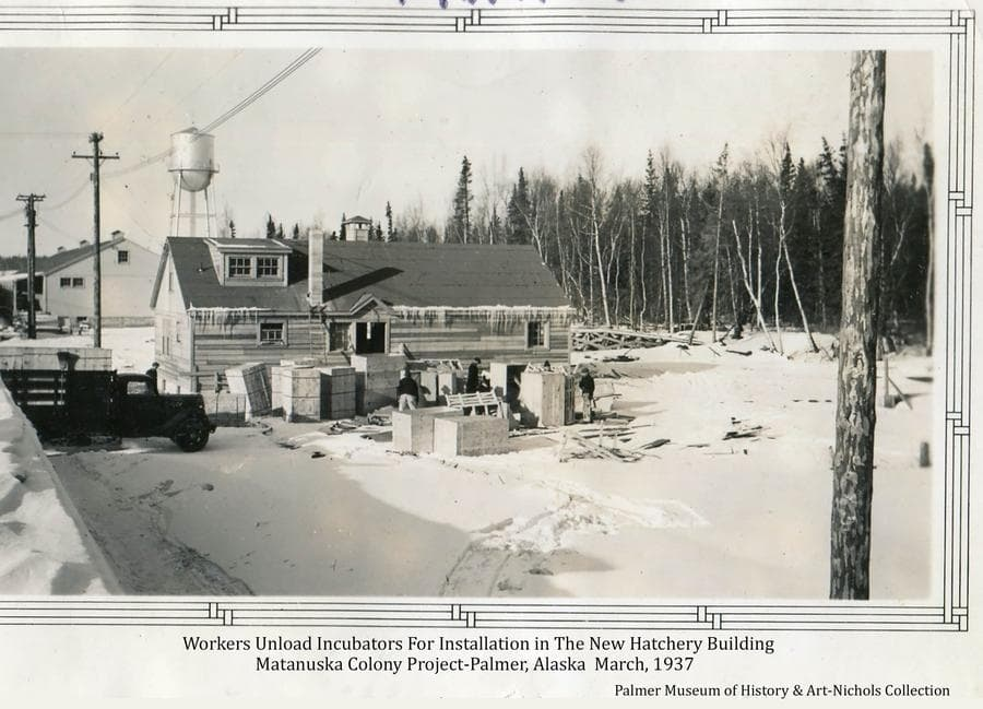 Image shows a winter scene of workers uncrating incubators for installation in the new poultry hatchery building in the community center of the Matanuska Colony Project in Palmer.  The Colony warehouse and water tower are visible in background.  Overhead electric lines are evident, dense forest is apparent at right and a truck is partially visible at left.