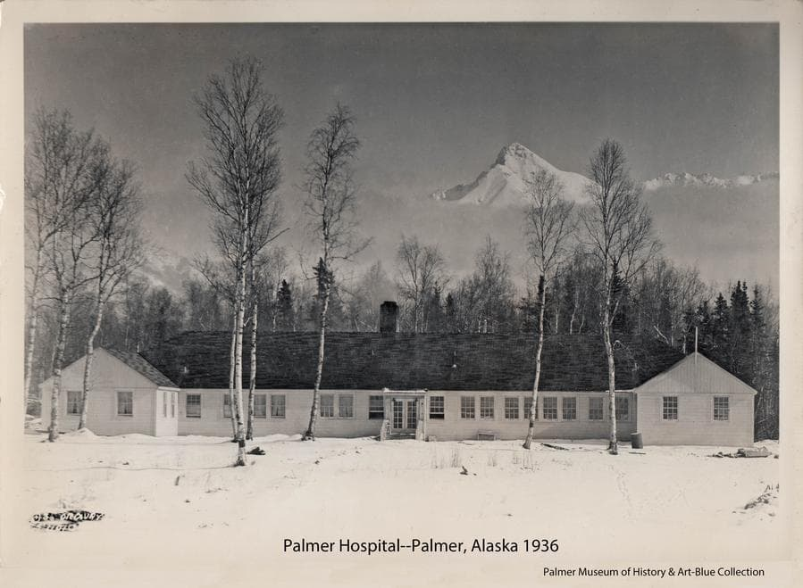 Image is of the west side of Palmer hospital in winter of 1936.  Scattered birch trees are in foreground and mountains in background with Byers Peak prominent above a cloud bank.