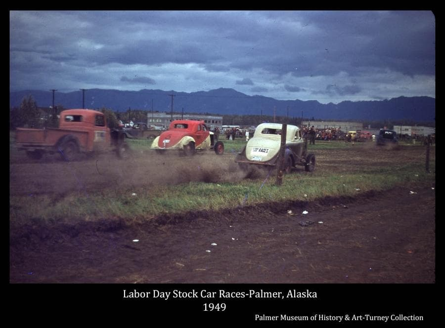 Image is of five stock cars racing on the Palmer Fairgrounds race track, identified as a Labor Day event.  Other automobiles and people are visible in middle ground with Palmer city buildings and Talkeetna Mountains beyond.