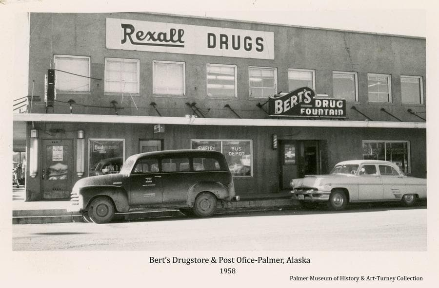 Image is an east side street view of the two storied Bert's Drugstore building exhibiting signs and window advertisements for a variety of businesses therein, including Rexall Drugs, Drug Fountain, Post Office, Barbershop, Bus Depot, Jewelry, Liquor Store and Bar.  Two automobiles are parked in front.