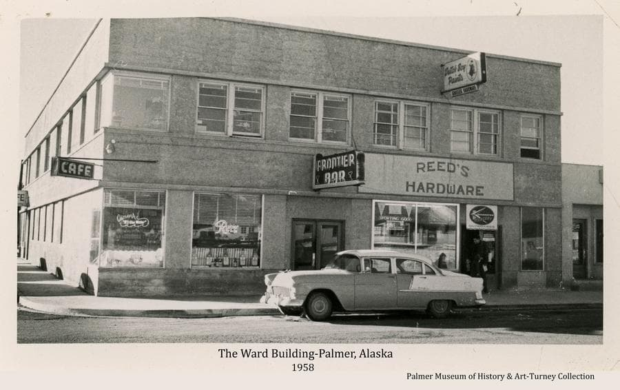 Image is of the east face street view of the Ward building in downtown Palmer.  Signs include advertisement for Reed's Hardware, Frontier Bar and a café.  A car is parked in front.