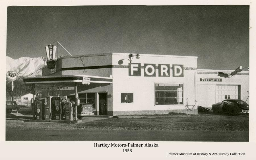 Image is the street view of the north and west facing sides of Hartley Motors Sales & Service Station building at the intersection of Old Glenn Highway and South Valley Way in Palmer as it appeared in fall of 1958.  Signs are evident advertising Ford automobiles, lubrication services and Chevron Oil products.  Gas pumps are visible in front of the building.   Automobiles are parked near the building. Snow-clad mountains are partially visible in background.  The street in front is newly paved.