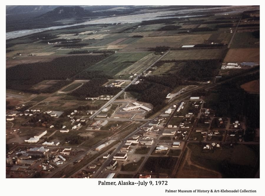 Image is a color aerial oblique view looking south across part of Palmer to the Springer System farm land, the Matanuska River and Bodenburg Butte.