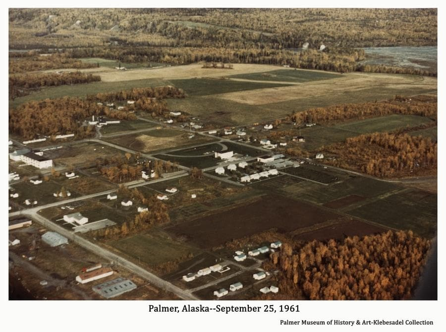 Image is a color aerial oblique view looking north across the east part of Palmer showing buildings, roads and farm land to the Matanuska River in background.