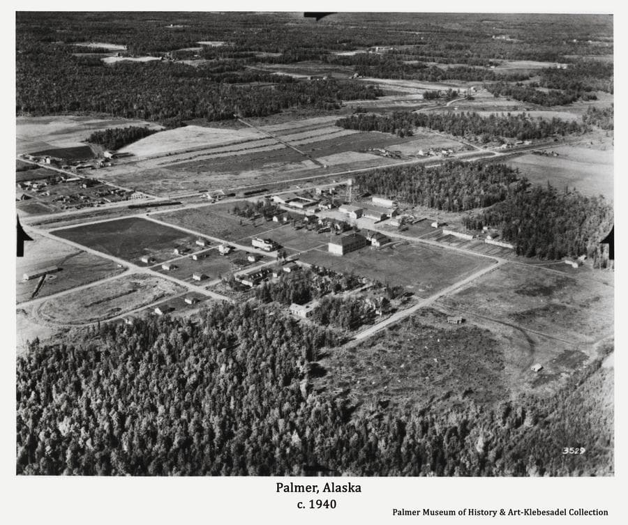 Image is an aerial oblique view looking northwesterly across the Community Center of Palmer showing buildings, roads and surrounding farm land and forest.