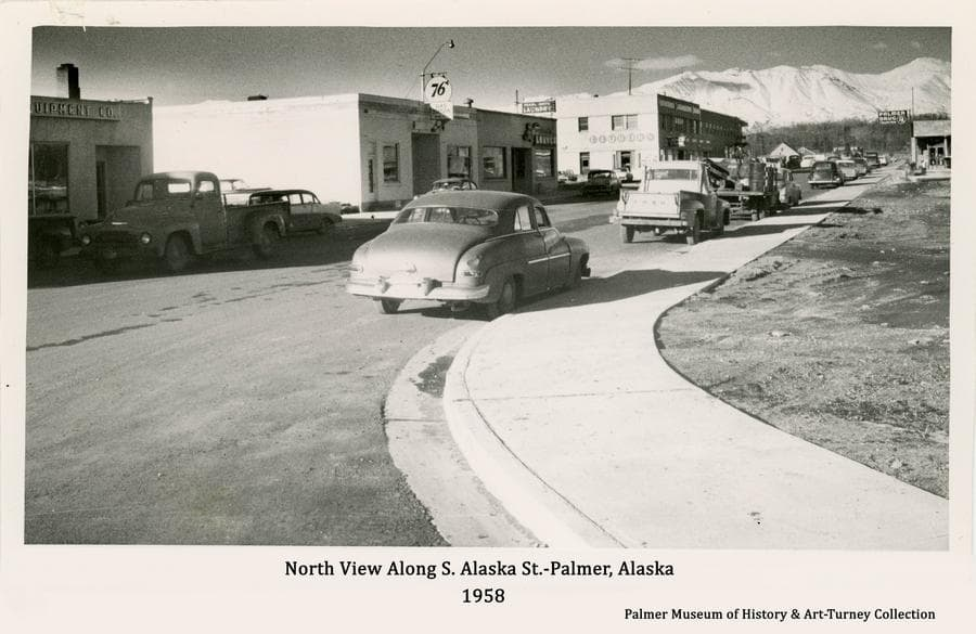 Image is the north view along South Alaska Street in Palmer, viewed from the intersection with W. Evergreen Ave., as it appeared in fall of 1958.   Automobiles are parked along newly installed curbs and sidewalks on the recently paves street.   Signs are evident and snow-clad Talkeetna Mountains are apparent in background.