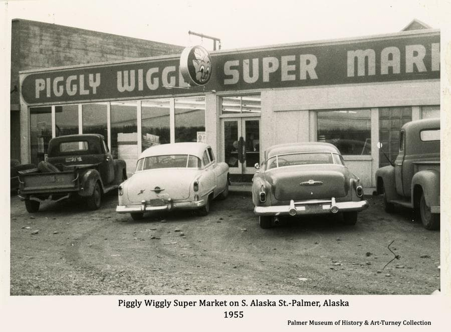 Image is of the Piggly Wiggly Super Market facing onto South Alaska Street in Palmer as it appeared in 1955.   Automobiles are parked in front and signs are evident.