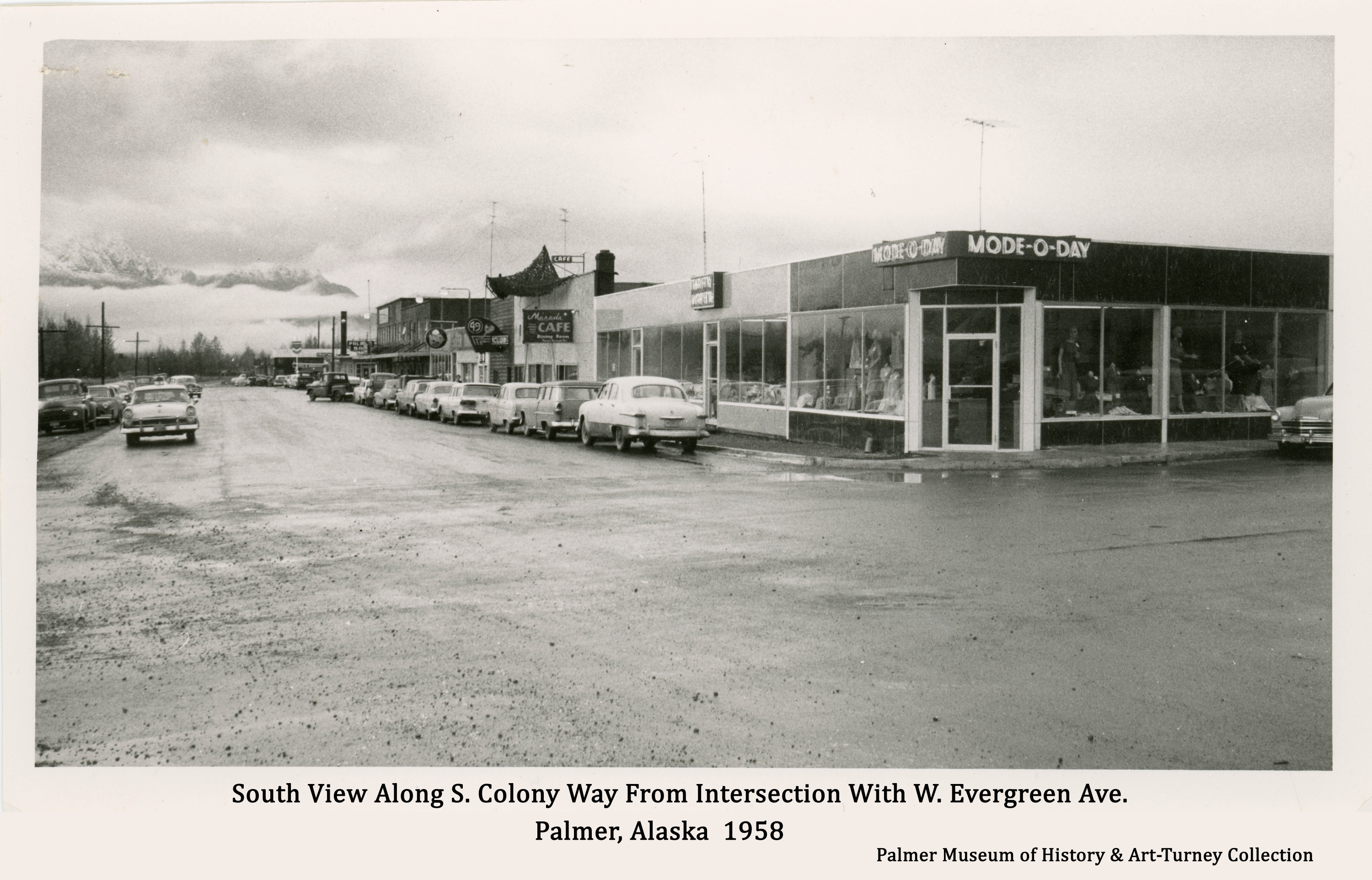 Image is the south view along South Colony Way in Palmer as it appeared in fall of 1958, viewed from the intersection with W. Evergreen Ave.   Automobiles are parallel parked on both sides of the street, signs are evident and tall TV antennas are visible.  The street is newly paved.