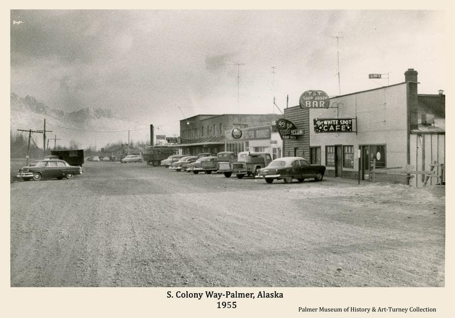 Image is the south view along South Colony Way in Palmer as it appeared in fall of 1955, viewed from near the intersection with W. Evergreen Ave.   Automobiles are angle parked on both sides of the street, signs are evident and tall TV antennas are visible on the roofs.
