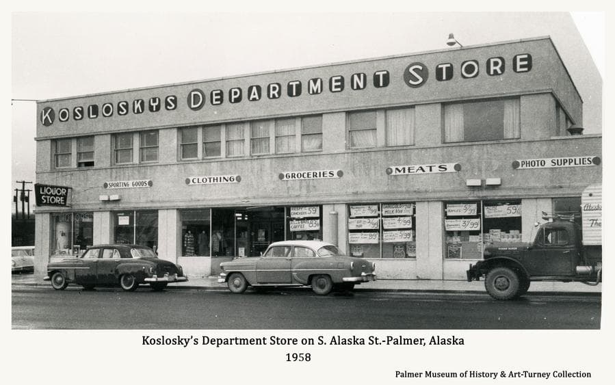 Image is the east side of Koslosky's Department Store facing South Alaska Street in Palmer as it appeared in fall of 1958.   Automobiles are parked along newly installed curbs and sidewalks on the recently paves street.   Signs are prominent.
