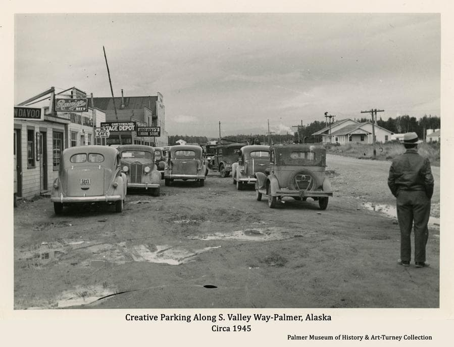 Image is a view of numerous automobiles parked in front of businesses along S. Valley Way.  A man stands in foreground looking away.   Many signs are visible.  The railroad depot is evident and two trains are visible nearby.
