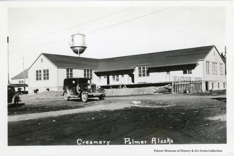 Image is a summer view of the Matanuska Valley Farmer's Co-op Creamery building in Palmer with exterior construction essentially complete but with foundation work still under way.  The water tower is visible behind and an ARRC car is in front.  A man is visible working on a retaining wall.