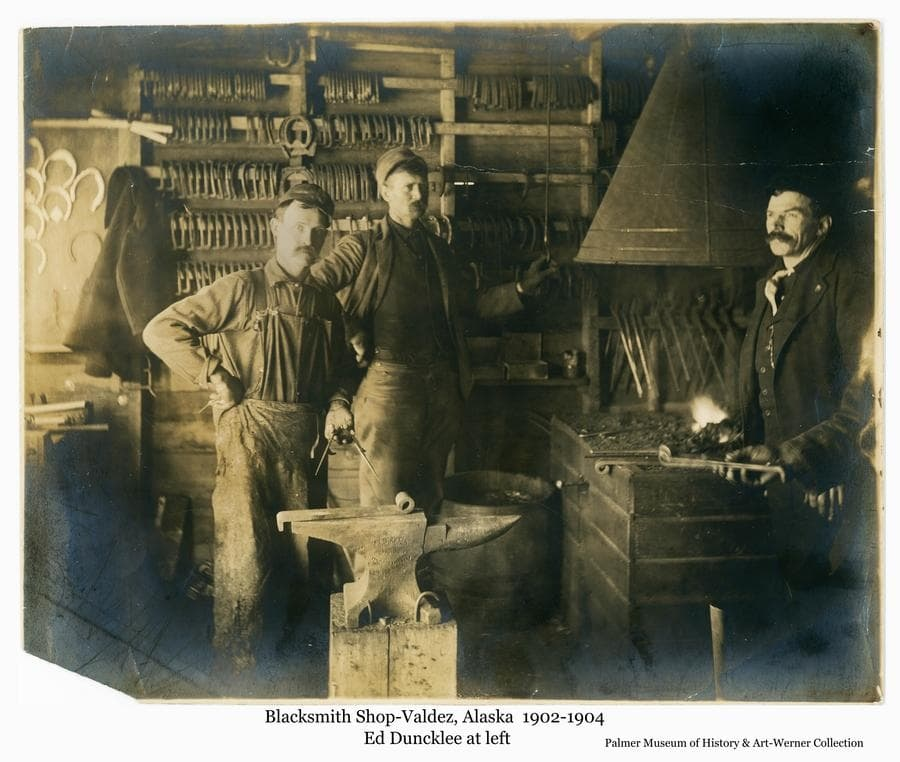 Image is a view of the inside of a blacksmith shop in Valdez showing three men standing near the forge and anvil with racks of horseshoes and tools on the wall behind.  The hand of a fourth man extends into the image at right holding an object they have apparently made.  The man at left in the photo is Ed Duncklee who would later take up a homestead in the Matanuska Valley which he later sold back to the government for inclusion in the Matanuska Colony project at Palmer.