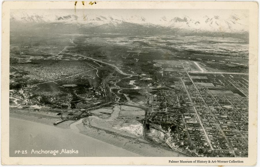 Image is an aerial view of Anchorage, Alaska taken from above Cook Inlet looking east over the Ship Creek valley and the city to snow-clad Chugach Mountains beyond.  The photo appears to have been take sometime between 1953 and 1964.