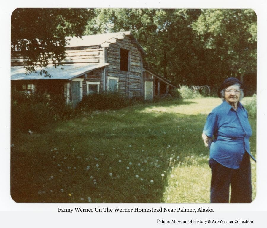 Image is of Fanny Werner standing on a portion of her Homestead farm with a log barn building and sheds behind her