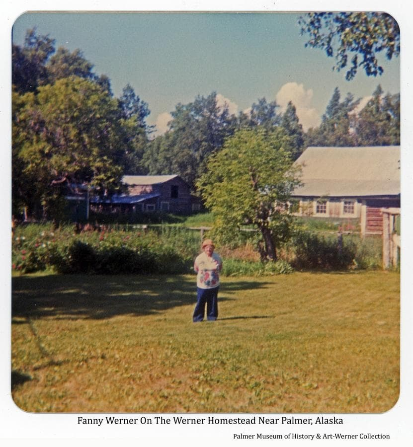 Image is of Fanny Werner standing on a field of her Homestead farm with log barn buildings, flowers and trees behind her.