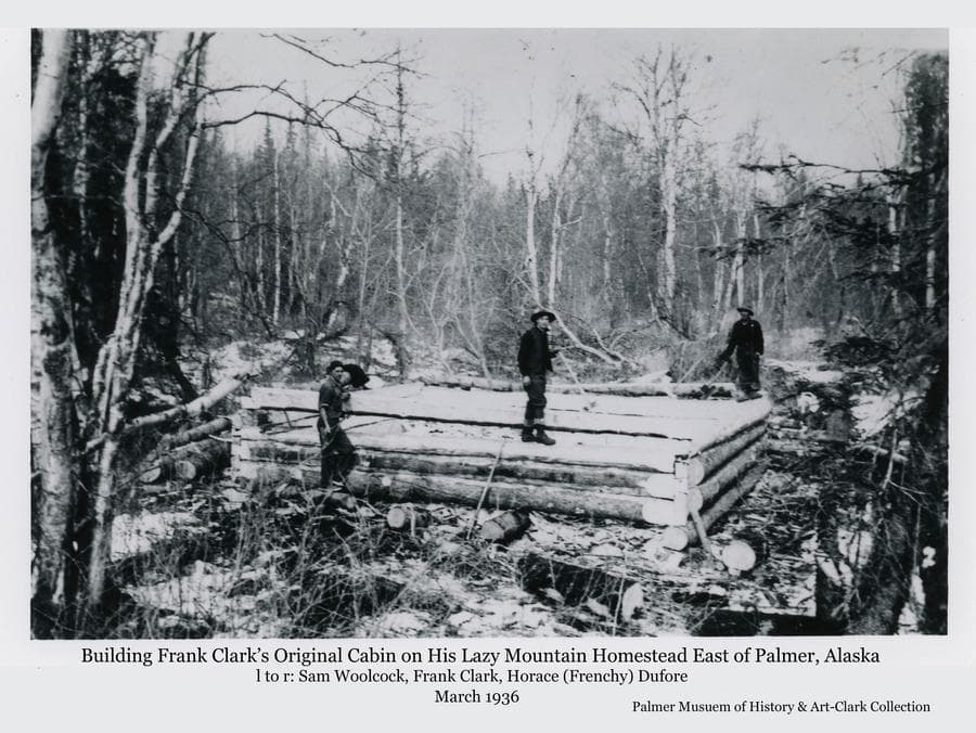 Image shows three men building a log house surrounded by dense forest.  Men are identified as (l to r) Sam Woolcock, Frank Clark, and Horace (Frenchy) Dufore.  The 166 acre Clark Homestead was located on the lower slope of Lazy Mountain above the Matanuska River east of Palmer.  Clark raised sheep and sold wool.
