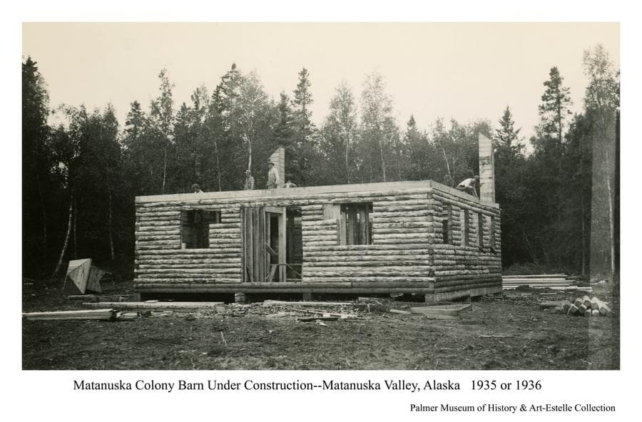 Image is a black & white view of a Matanuska Colony barn under construction.  The lower portion, constructed of spruce logs, is essentially complete with two corner air shafts to the upper hay mow in place.  Several men are visible preparing to construct the hay mow floor and roof using dimension lumber.  The cupola, ready to be installed as ventilation at the peak of the roof, is visible on the ground at left.